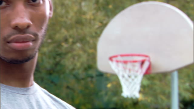 panning shot of serious man with basketball hoop - see other clips from this shoot 1281 stock videos and b-roll footage