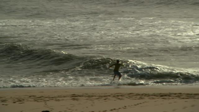 vídeos y material grabado en eventos de stock de panning shot of silhouette man surfboarding in sea during vacation on sunny day - figueira da foz, portugal - deporte acuático