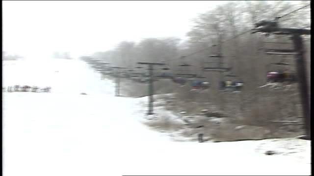 panning shot of skiers on lift riding mountain and crowd watching in killington, vermont - freistil skifahren stock-videos und b-roll-filmmaterial