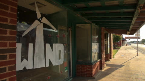 panning shot of small town to a wind energy store front window - schwenk stock-videos und b-roll-filmmaterial