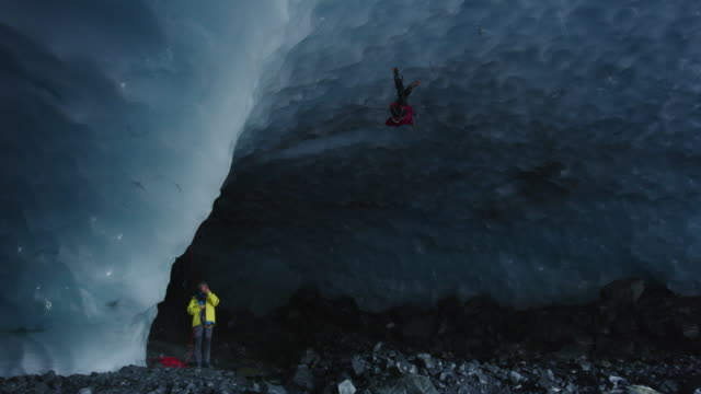 Panning shot of spotter watching climber in ice cave using rope and hooks / Palmer, Alaska, United States