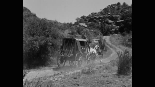 panning shot of stagecoach driver riding stagecoach on dirt track - horsedrawn stock videos & royalty-free footage