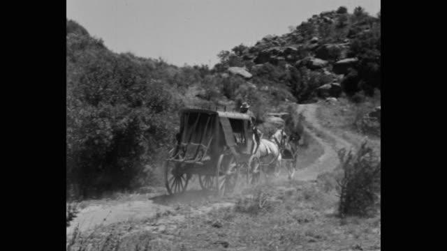 vidéos et rushes de panning shot of stagecoach driver riding stagecoach on dirt track - voiture hippomobile