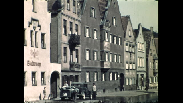 """panning shot of street, buildings on one side with the word """"gladtwaage """" and cars parked by the sidewalk; people walking on the sidewalk - orthographic symbol stock videos & royalty-free footage"""