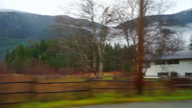 panning shot of structures and vehicles by trees near mountains against sky - cheakamus lake, british columbia - garibaldi park stock videos & royalty-free footage