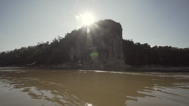 panning shot of sun shining over rocky cliff by river against sky, scenic view of remote location on sunny day - luang prabang, laos - remote location bildbanksvideor och videomaterial från bakom kulisserna