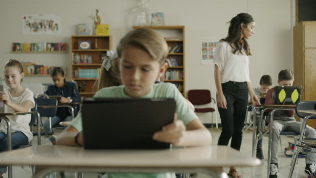 Panning shot of teacher assisting children in classroom reading digital tablets / Provo, Utah, United States