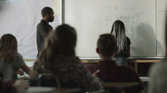 panning shot of teacher high-fiving student solving equation on whiteboard / provo, utah, united states - female high school student stock videos & royalty-free footage