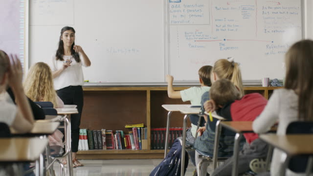 Panning shot of teacher questioning students in classroom / Provo, Utah, United States