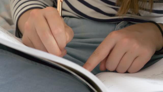 Panning shot of teenager doing homework, writing in text book.
