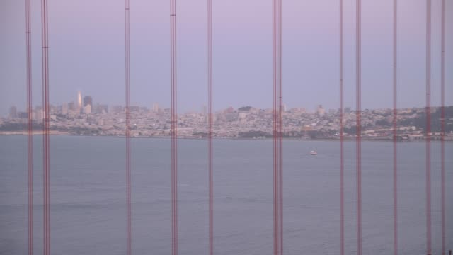 panning shot of the golden gate bridge and city in background at dusk, san francisco, california, united states of america, north america - golden gate bridge stock-videos und b-roll-filmmaterial