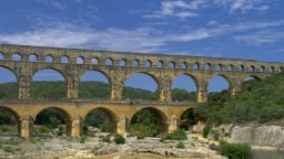 Panning shot of the Pont du Gard, ancient Roman aqueduct in the Southern France, with beautiful blue cloudy skies in the background. 4K, UHD