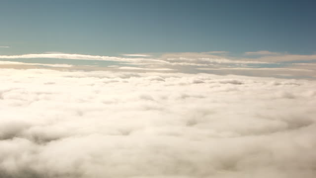 a panning shot of the top of a beautiful blanket of clouds. - heaven stock videos & royalty-free footage