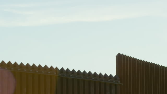 panning shot of the tops of the steel-slat border wall between mexico and the united states on a bright, sunny day (shot from the us side) - international border barrier stock videos & royalty-free footage