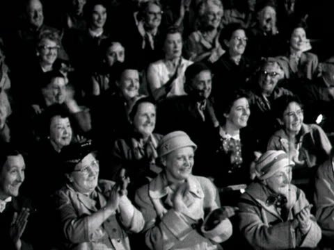 Panning shot of theatre audience clapping enthusiastically 1958 NB scratches visible on film