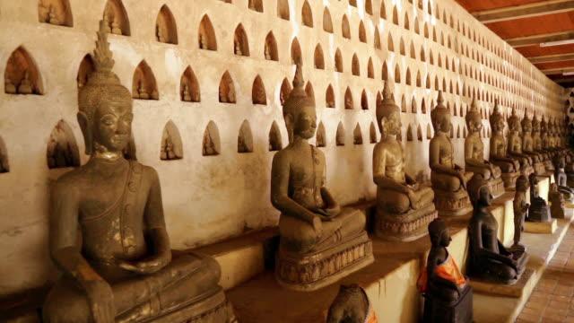vidéos et rushes de panoramique à coup de milliers de statues de bouddha au wat si saket, vientiane, laos - assis en tailleur