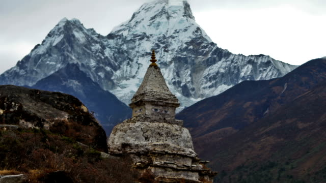 Panning shot of Time-lapse of a buddhist stupa with Ama Dablam peak in the background.