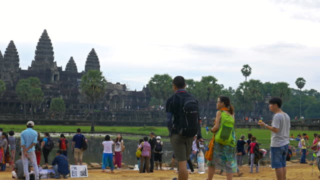 Panning shot of tourists viewing the towers of Angkor Wat