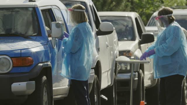 vídeos y material grabado en eventos de stock de toma de panoramización de dos enfermeras femeninas que llevan batas, máscaras faciales quirúrgicas, guantes y escudo facial hablando con los pacientes en sus coches en una línea de pruebas covid-19 (coronavirus) covid-19 (coronavirus) fuera de una clí - trabajador de primera línea
