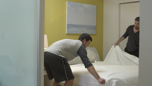 Panning shot of two men changing sheet on bed