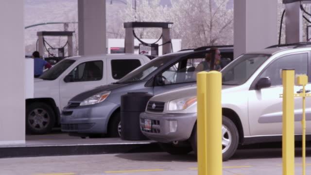vidéos et rushes de panning shot of vehicles at a gas station. - plan large