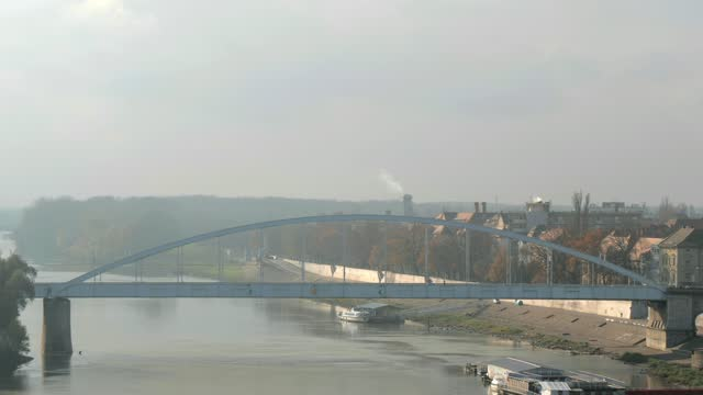 4k panning shot of votive church and cathedral of our lady of hungary, river tisa and szeged bridge - セゲド点の映像素材/bロール