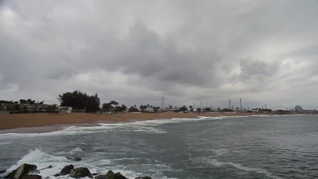 panning shot of waves crashing on rocks/ abidjan/ ivory coast - côte d'ivoire stock videos & royalty-free footage