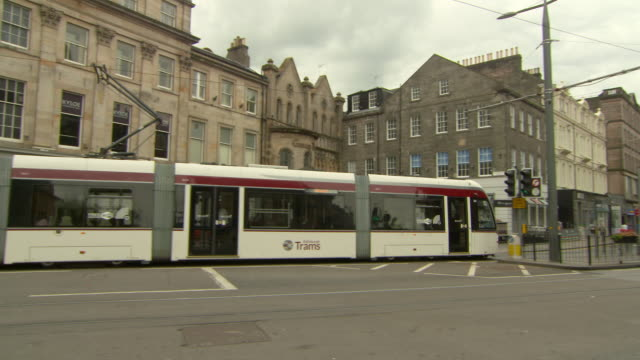 panning shot of white tram moving on street by buildings in city against sky - edinburgh, scotland - tram stock videos & royalty-free footage
