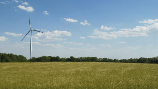 Panning shot of wind turbine in field