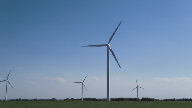 Panning shot of wind turbines in field