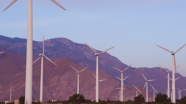 Panning shot of wind turbines turning in the wind