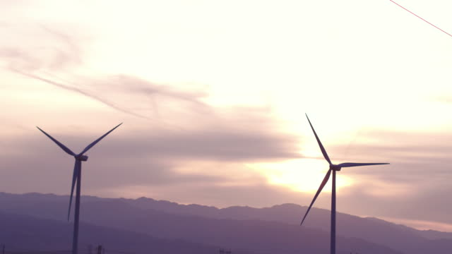 panning shot of wind turbines turning in the wind - back lit video stock e b–roll
