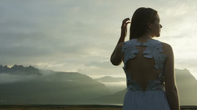 panning shot of woman in dress taking in the view in Iceland