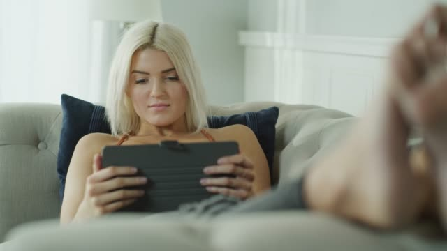 panning shot of woman laying on sofa reading digital tablet / cedar hills, utah, united states - electronic book stock videos & royalty-free footage
