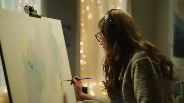vídeos de stock, filmes e b-roll de panning shot of woman listening to headphones and painting on canvas / cedar hills, utah, united states - pintor artista