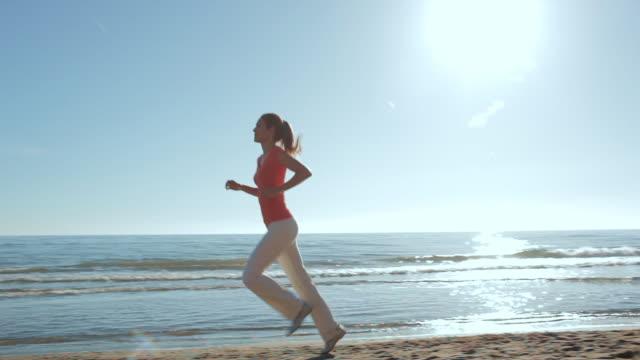 Panning shot of woman running on beach/Marbella region, Spain
