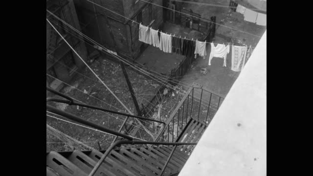 panning shot of woman running through backyard tenement with clothes drying on it - hanging stock videos & royalty-free footage