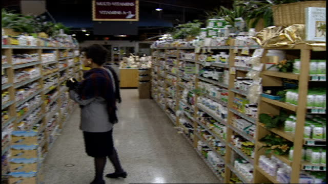 panning shot of woman shopping in grocery aisle to bottle of herbal suppliments on shelf in san antonio tx - homeopathic medicine stock videos and b-roll footage
