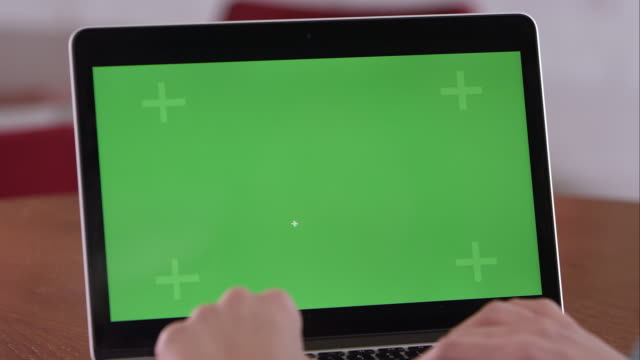 Panning shot of woman using computer with green screen.