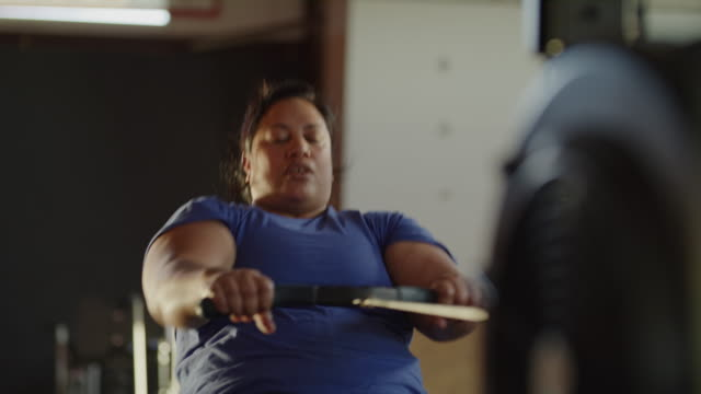 panning shot of woman using rowing machine in gymnasium / lehi, utah, united states - overweight active stock videos & royalty-free footage
