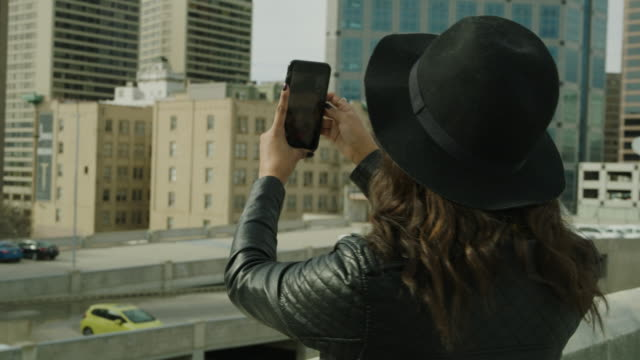panning shot of woman video chatting with cell phone on urban roof / salt lake city, utah, united states - multi storey stock videos & royalty-free footage
