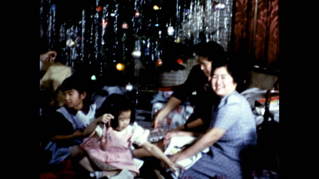 panning shot of women and children sitting under the christmas tree opening presents - 1930 1939点の映像素材/bロール