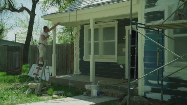 panning shot of worker painting porch of house / spring city, utah, united states - house painter stock videos and b-roll footage
