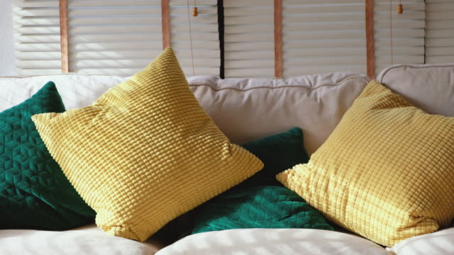 panning shot of yellow and green pillow on white sofa in living room - domestic room stock videos & royalty-free footage