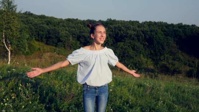 Panning shot of young girl spreading hands with joy and inspiration facing the sun