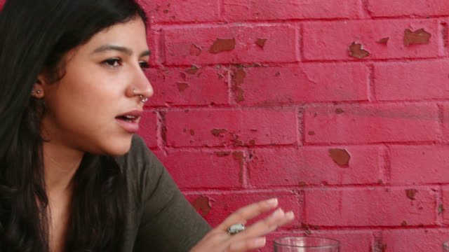 stockvideo's en b-roll-footage met panning shot of young woman and man happily talking at outdoor café - hanenkam haardracht