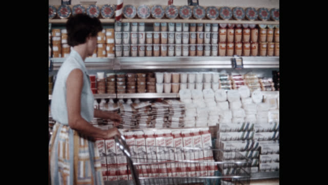 panning shot of young woman buying milk carton from supermarket - packaging stock videos & royalty-free footage