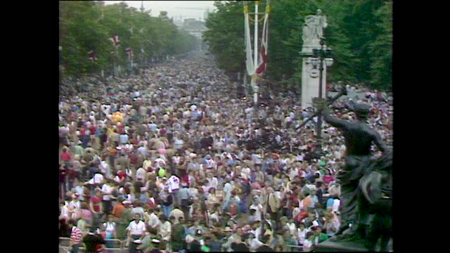 panning shot over a large crowd cheering and singing outside buckingham palace and the mall on the day of the wedding of prince charles and lady... - english culture stock videos & royalty-free footage
