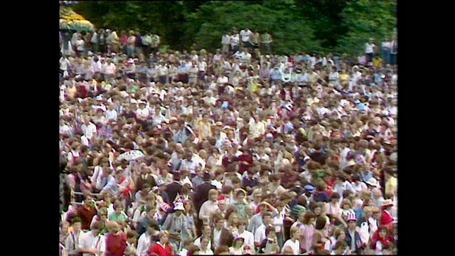 panning shot over crowds of people outside buckingham palace chanting on the day of the wedding of prince charles and lady diana spencer; 1981. - crowd stock videos & royalty-free footage