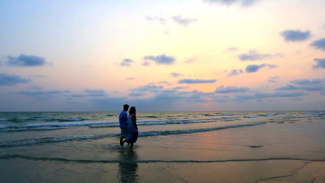 Toma panorámica: Pareja romántica caminando en la playa al atardecer